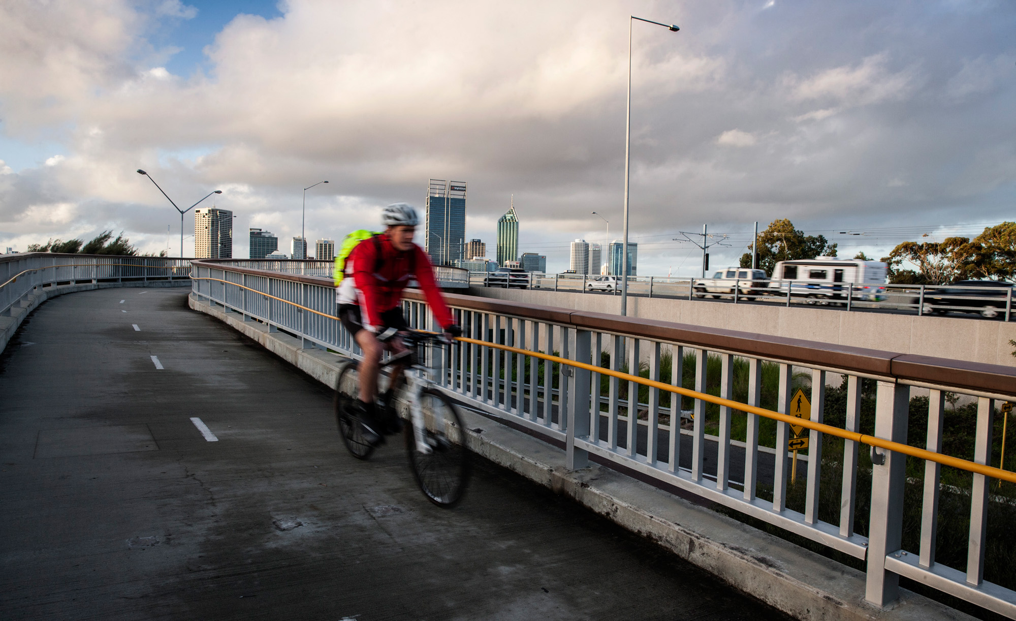 Man cycling on bike path beside freeway